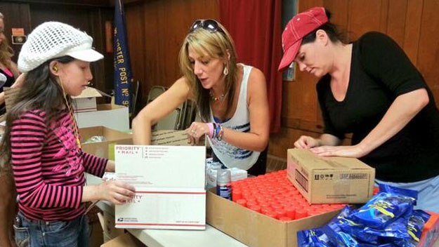 Heartillery Group and Hero Helpers of America combine efforts to form a care package production line at the American Legion Hall in Foxboro